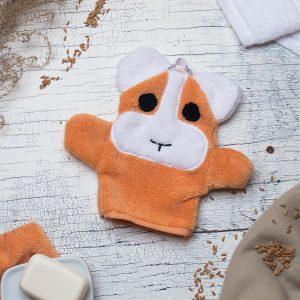 Hamster Waschhandschuh orange und weiß Flatlay mit Dinkel Körnern und Seife als Deko