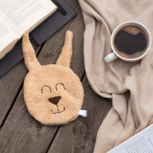 Hase Körnerkissen braun mit Decke, Buch und Kaffee auf Holzuntergrund